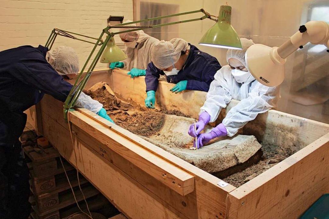 Der Bleisarg wird unter Laborbedingungen freigelegt.    Foto: Ronald Simke/Augusta Raurica