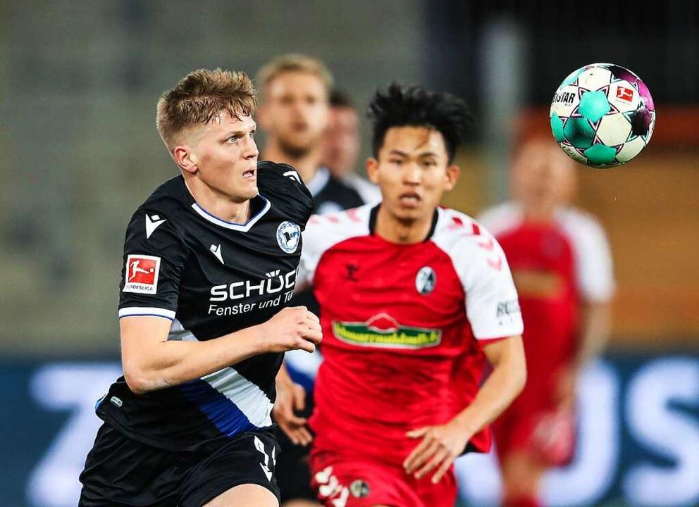 Bielefelds Joakim Nilsson und Freiburgs Woo-Yeong Jeong (r) in Aktion.  | Foto: Friso Gentsch (dpa)