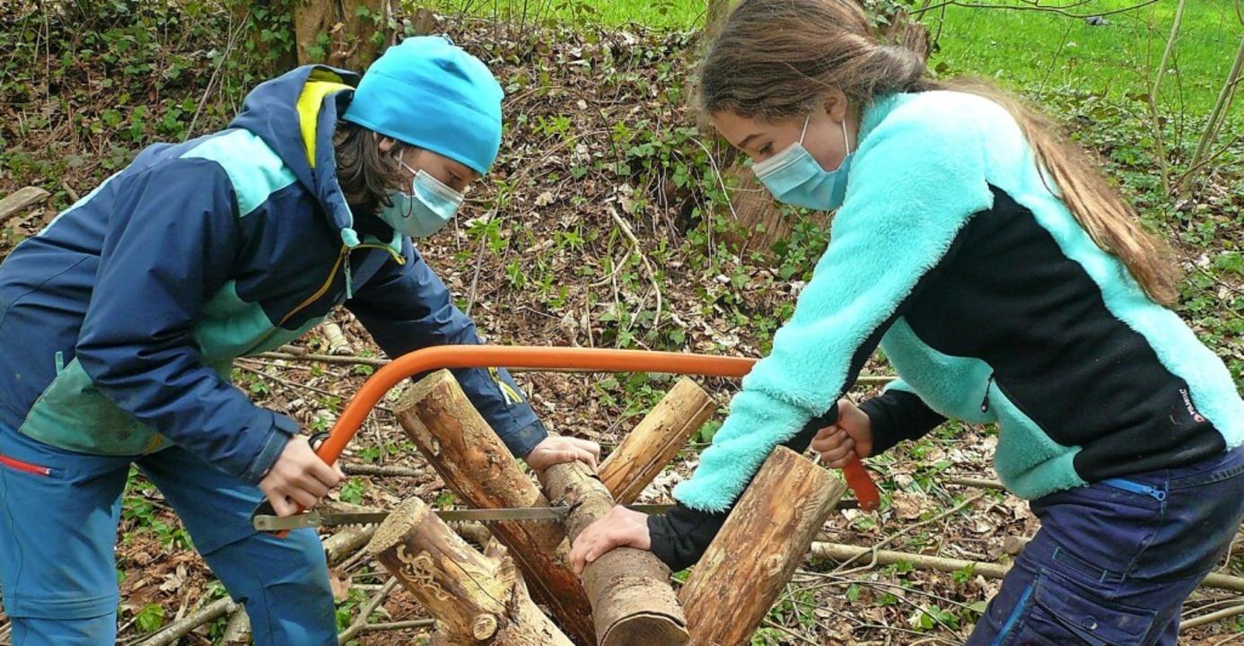 Noemie (links) und Sveva sägen Holz fürs Feuer.  | Foto: Nina Herrmann