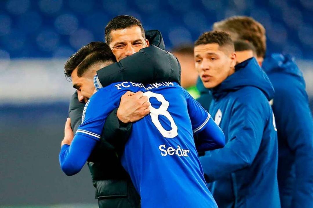 Schalke-Trainer Dimitrios Grammozis umarmt Mittelfeldspieler Suat Serdar.    Foto: LEON KUEGELER (AFP)