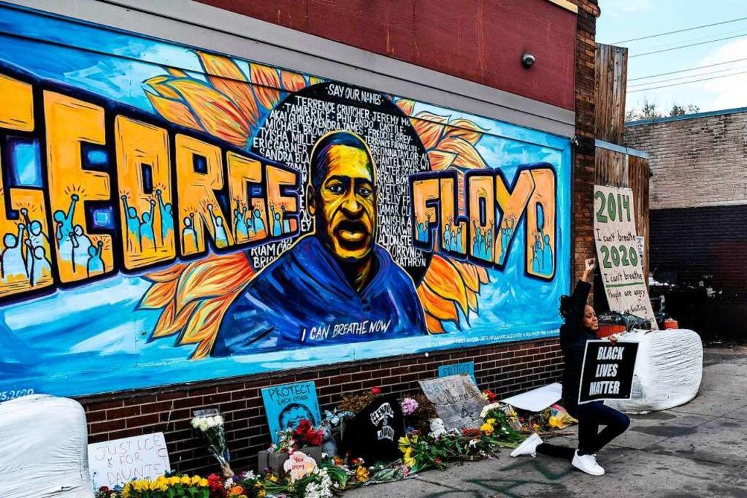 Vor einem Wandgemälde, das Floyd zeigt, haben Menschen Blumen niedergelegt.  | Foto: CHANDAN KHANNA (AFP)