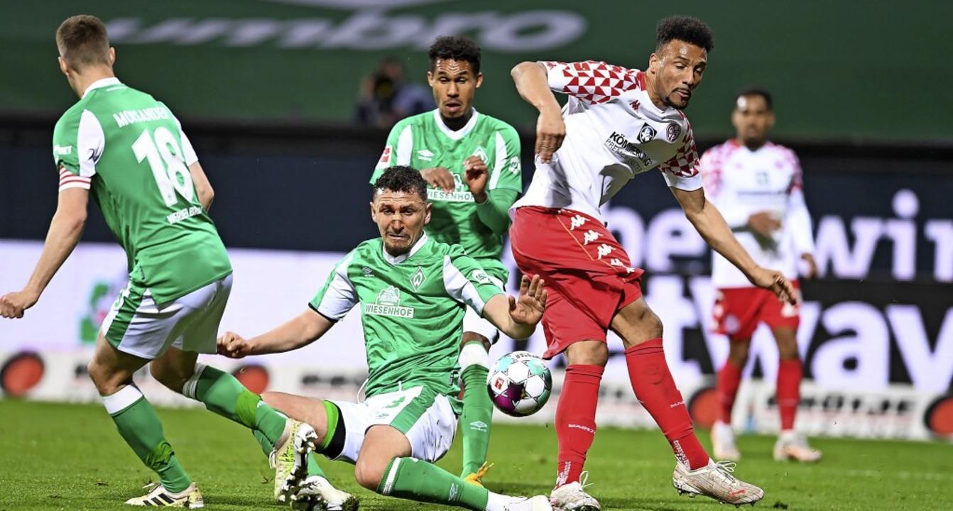 Abstiegskampf: die  Werder-Akteure (vo...lassie gegen den Mainzer Karim Onisiwo    Foto: Carmen Jaspersen (dpa)