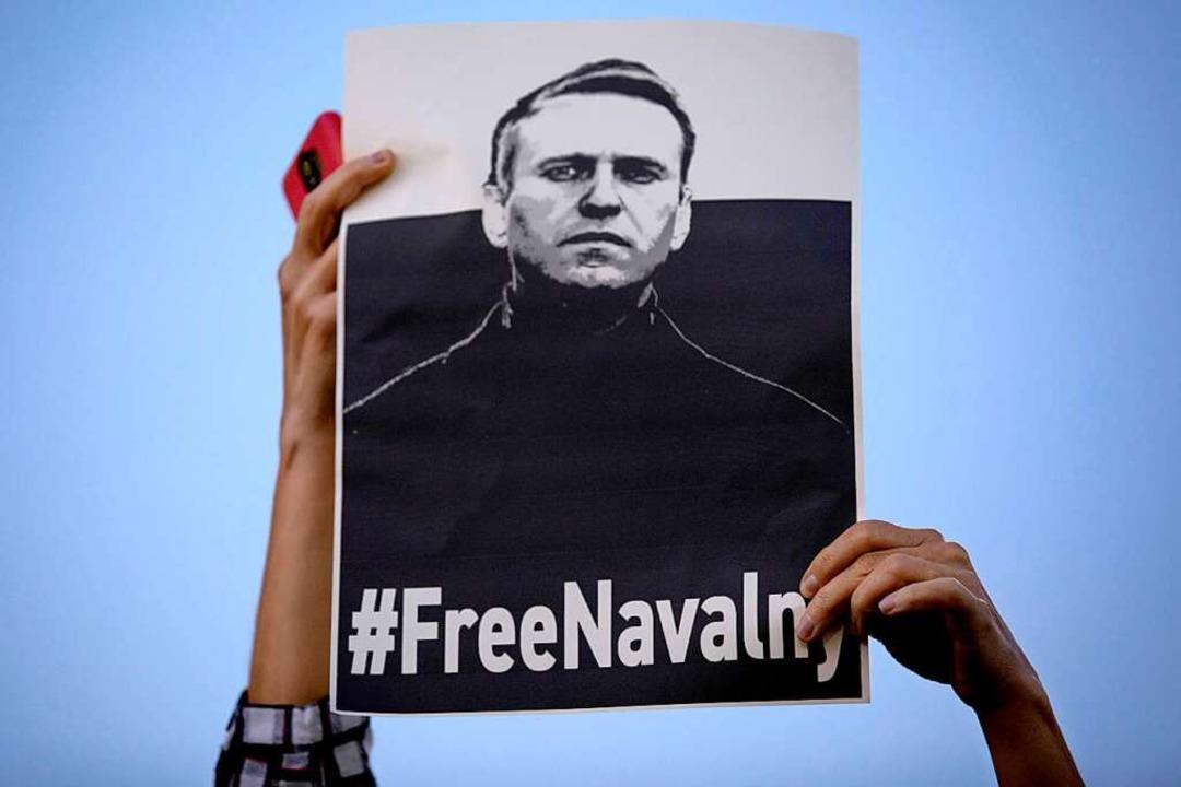 Eine Frau hält ein Schild mit der Aufs...russischen Oppositionsführers Nawalny.  | Foto: Oded Balilty (dpa)