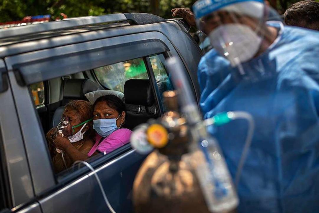 Beatmung auf der Straße: Eine Frau wird in einem Auto mit Sauerstoff versorgt.     Foto: Altaf Qadri (dpa)