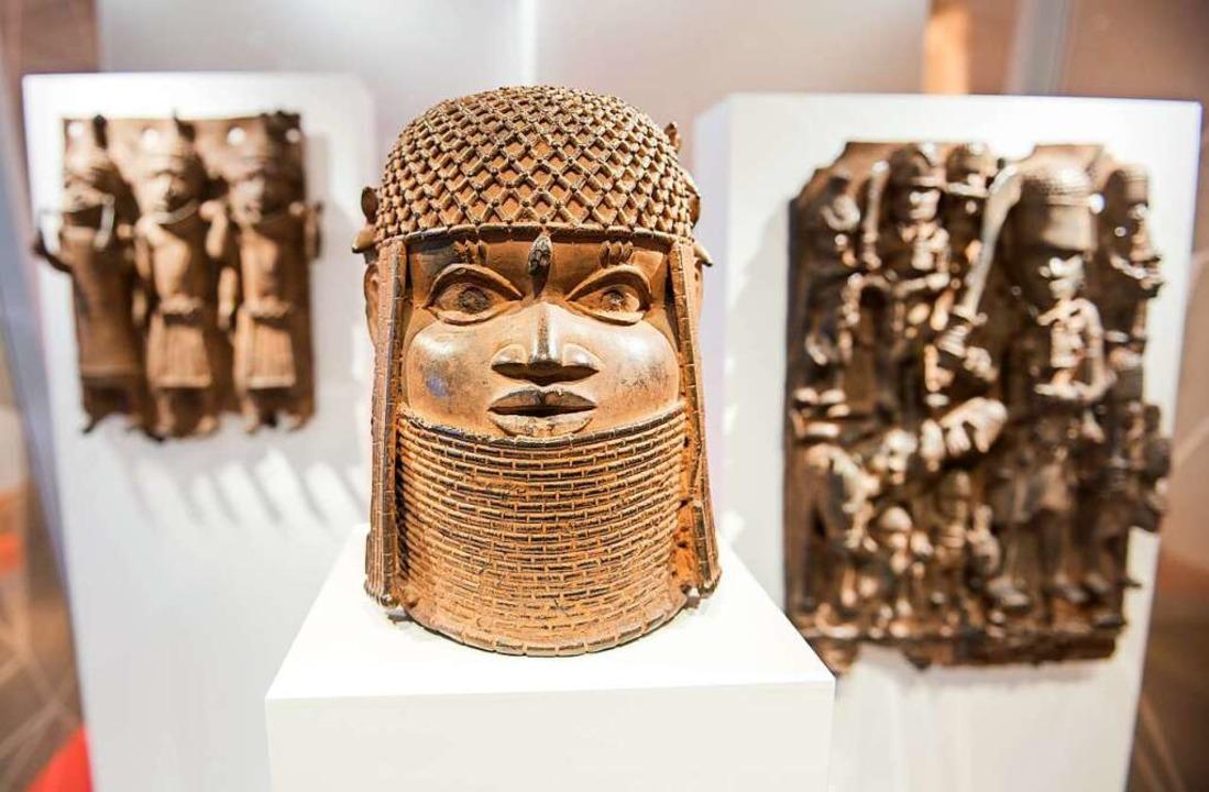 Drei Raubkunst-Bronzen aus dem Benin i... Gewerbe in einer Vitrine ausgestellt.    Foto: Daniel Bockwoldt (dpa)
