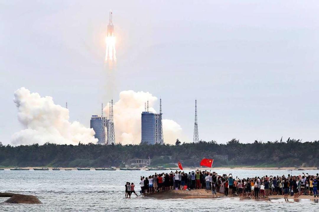 Begeistert beobachten Zuschauer auf de...sel Hainan den Start der Trägerrakete.  | Foto: Jin Liwang (dpa)