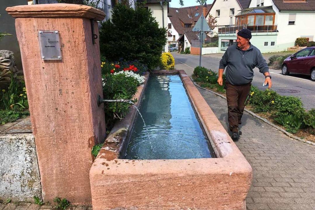 Ebringens Wassermeister Harald Klein a...en Dorfbrunnen an der Schönbergstraße.  | Foto: Nina Herrmann