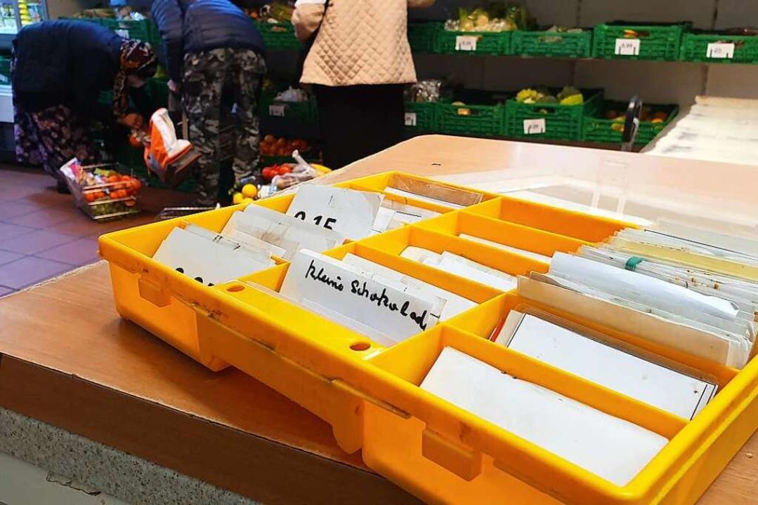 Auf handgeschriebenen Zetteln stehen Warennamen und -preise.    Foto: Theresa Steudel