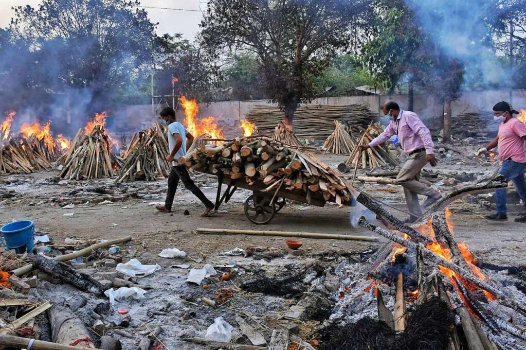 Ein Arbeiter zieht Holz auf einem Hand...ematorien und Krankenhäuser überfüllt.  | Foto: Ishant Chauhan (dpa)
