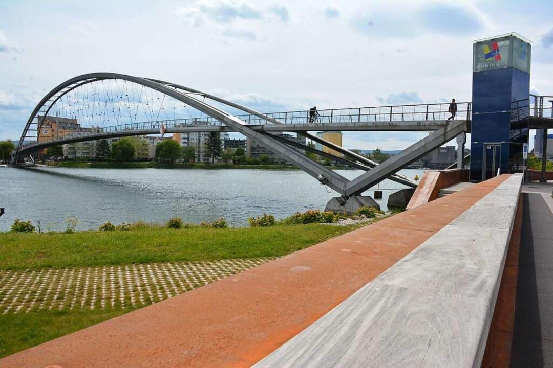 Eine ellenlange Sitzbank am Rheinufer beidseits der Dreiländerbrücke  | Foto: Hannes Lauber