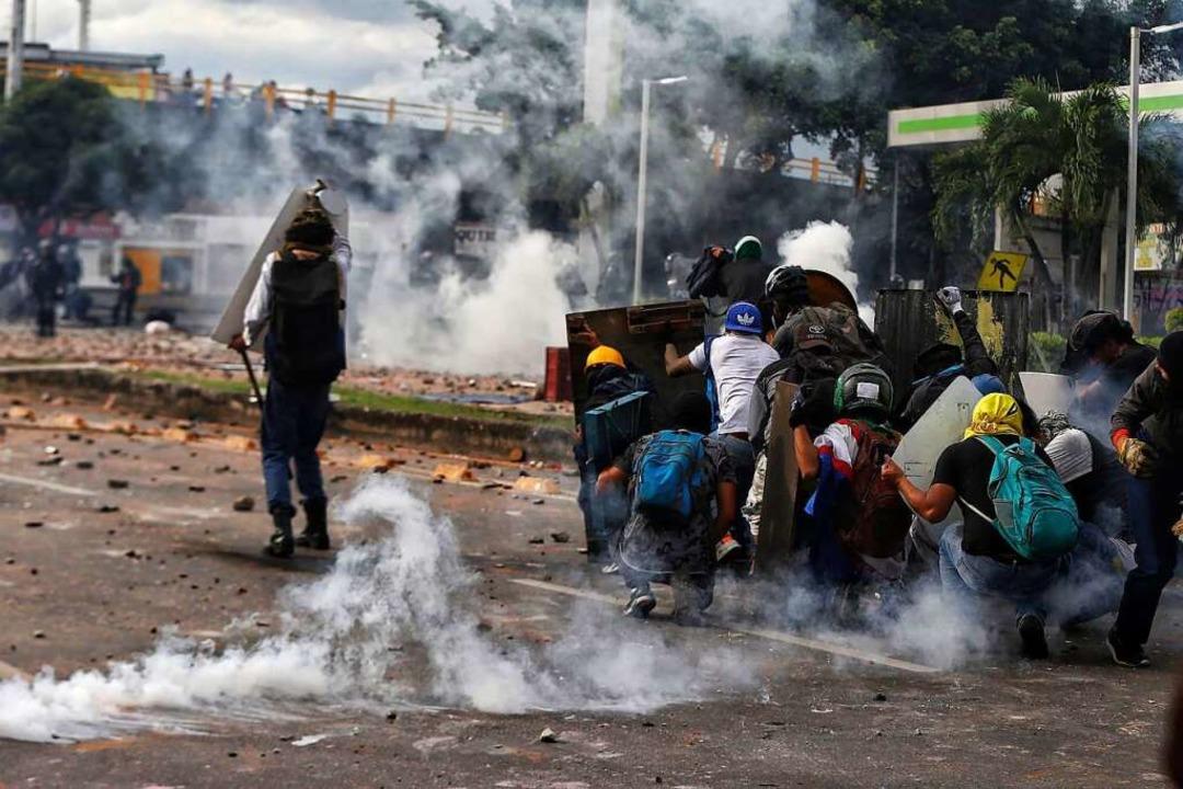 Demonstranten verschanzen sich beim Aufeinandertreffen mit der Polizei.  | Foto: Andres Gonzalez (dpa)