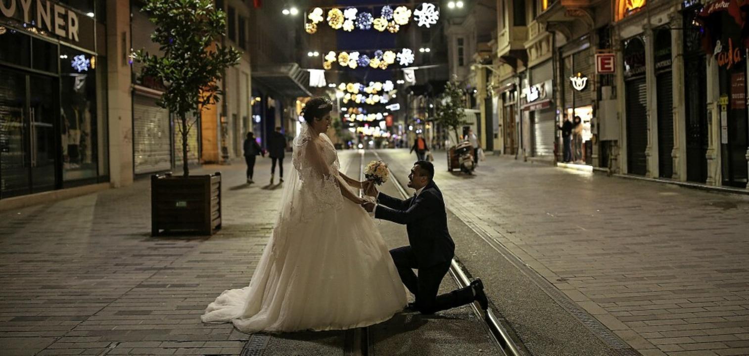 Frisch verheiratetes Paar  auf einer w...ast menschenleeren Straße in Istanbul.    Foto: Emrah Gurel (dpa)
