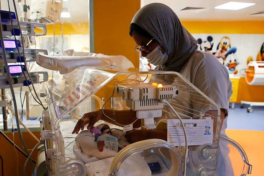 Eine Krankenschwester kümmert sich an ...r Kaiserschnitt zur Welt gebracht hat.    Foto: Abdeljalil Bounhar (dpa)