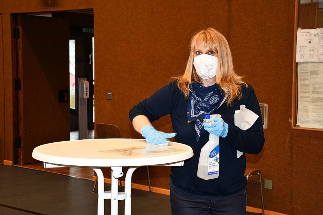 Helfer desinfizieren die Tische    Foto: Tanja Bury