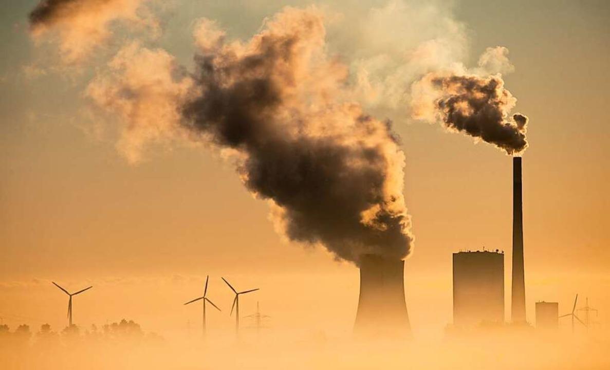 Das Kohlekraftwerk Mehrum in Niedersachsen und Windräder produzieren Strom.    Foto: Julian Stratenschulte (dpa)