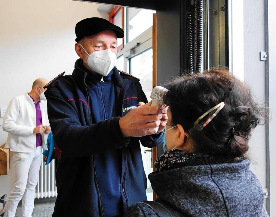 Fiebermessung vor der Impfung durch Angehörige der  Feuerwehr.  | Foto: Gudrun Gehr