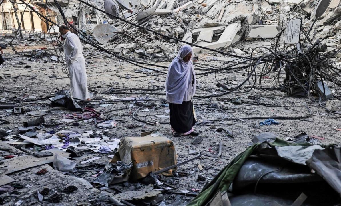 Palästinenser laufen durch die Trümmer...örten Al-Sharouk-Towers in Gaza-Stadt.  | Foto: MOHAMMED ABED (AFP)