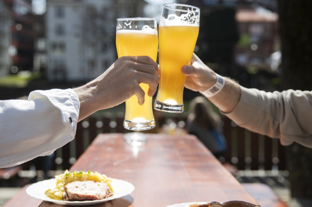Wieder möglich: Zwei Menschen sitzen b...ergarten und stoßen mit einem Bier an.  | Foto: Tom Weller (dpa)