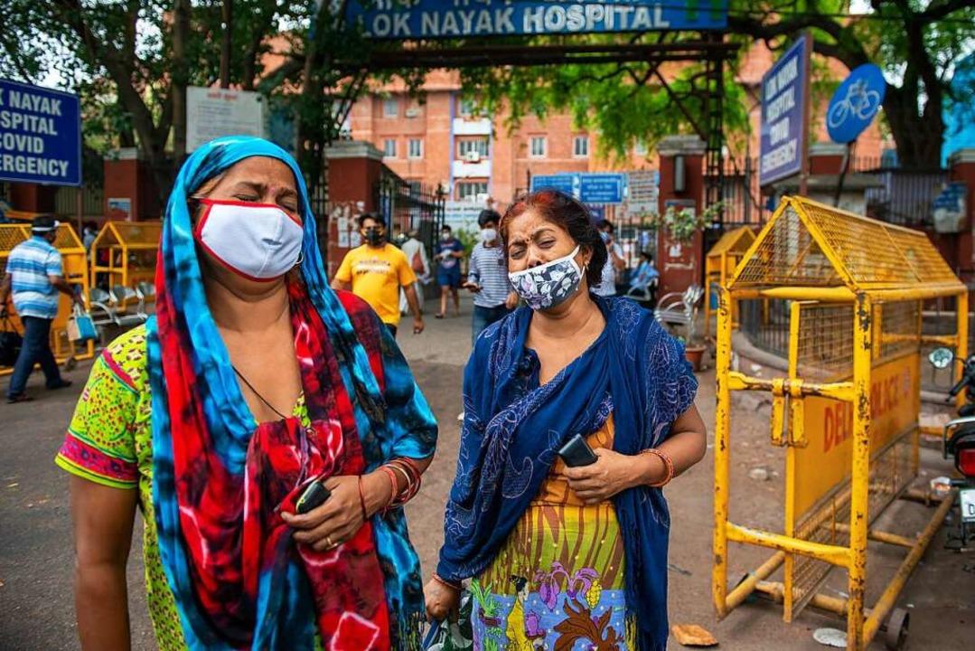 Zwei Frauen betrauern den Tod eines Fa...nmitglieds vor dem Lok Nayak Hospital.  | Foto: Pradeep Gaur (dpa)