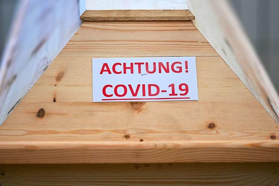 Die Aufschrift auf dem Sarg warnt vor  der Krankheit Covid-19.  | Foto: Felix Kästle