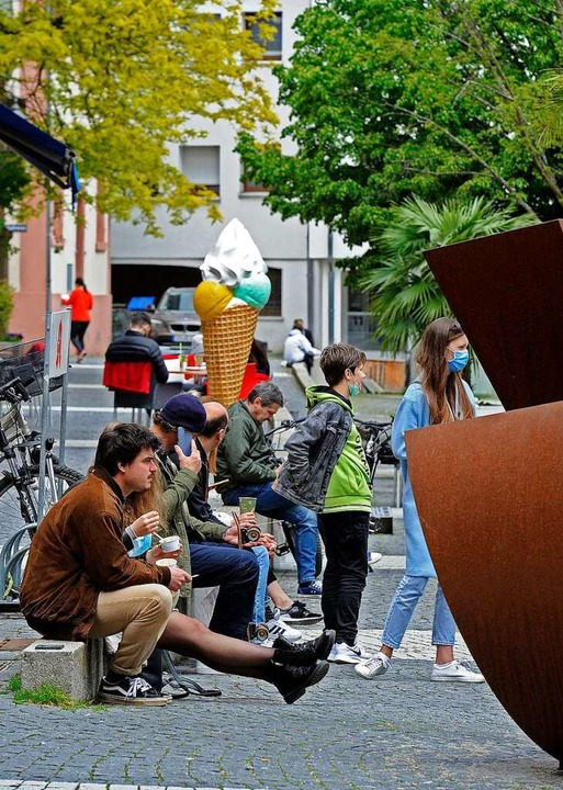 Einige sitzen mit ihrem Eis auf dem Urteilsplatz vor dem  Café.  | Foto: Bettina Schaller