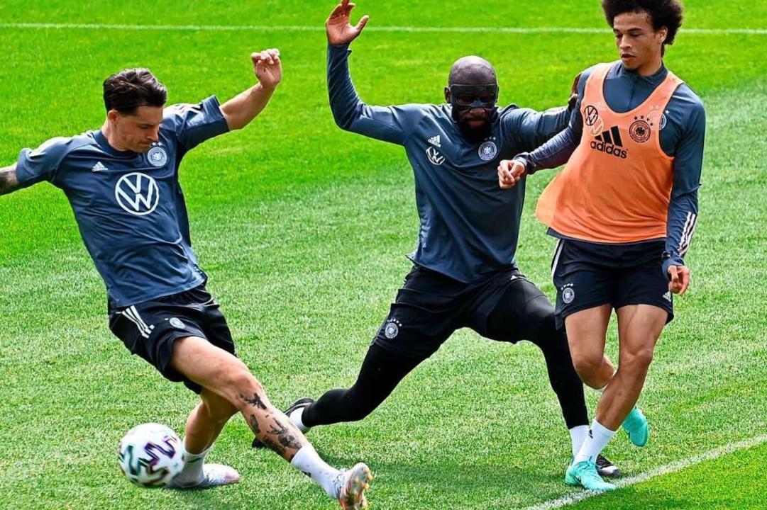 Im Trainingseifer: die deutschen Natio...n Koch, Antonio Rüdiger und Leroy Sané  | Foto: CHRISTOF STACHE (AFP)