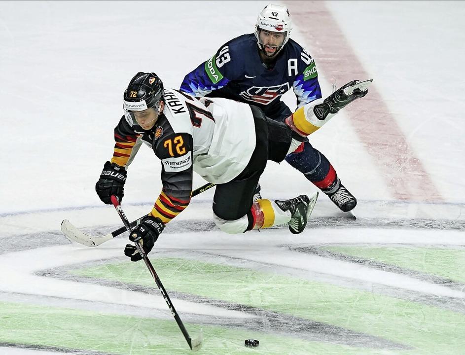 Luftnummer: Der Deutsche Dominik Kahun... Colin Blackwell aus den USA aufs Eis.    Foto: Roman Koksarov (dpa)