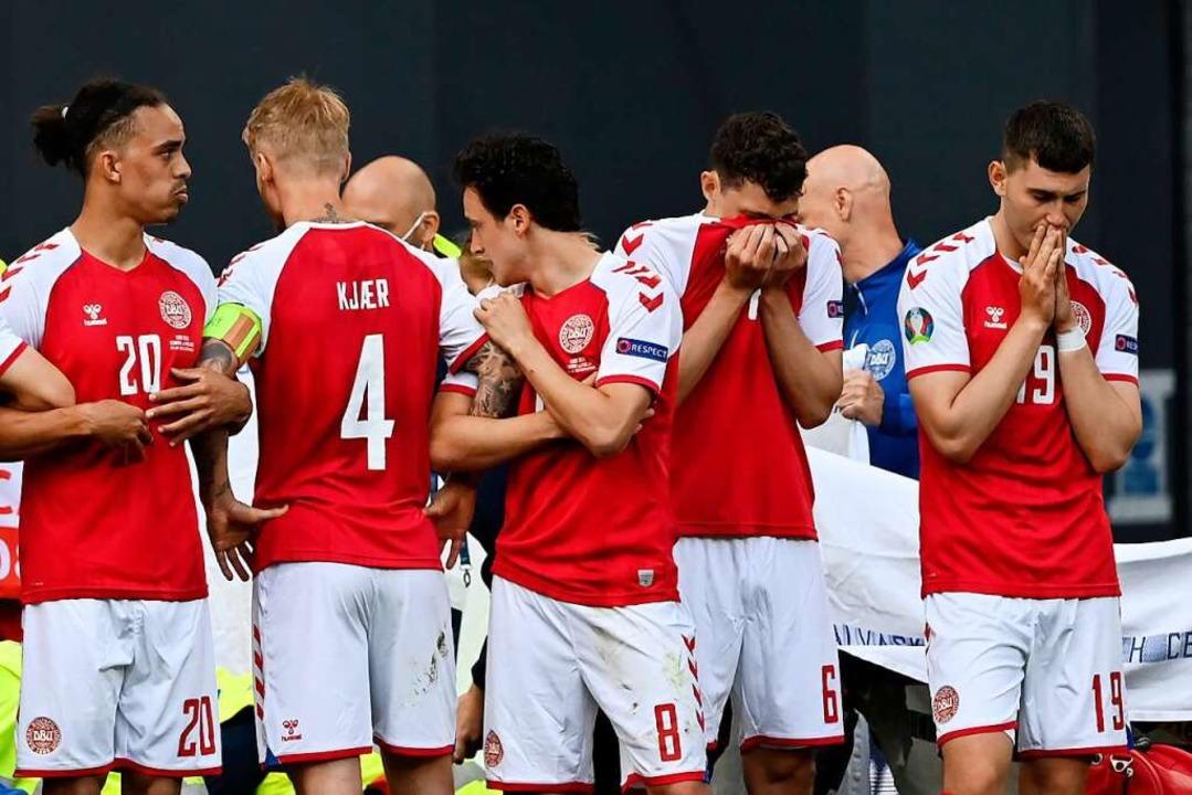 Den Mitspielern von Christian Eriksen ...n, während ihr Kollege behandelt wird.  | Foto: Stuart Franklin (dpa)