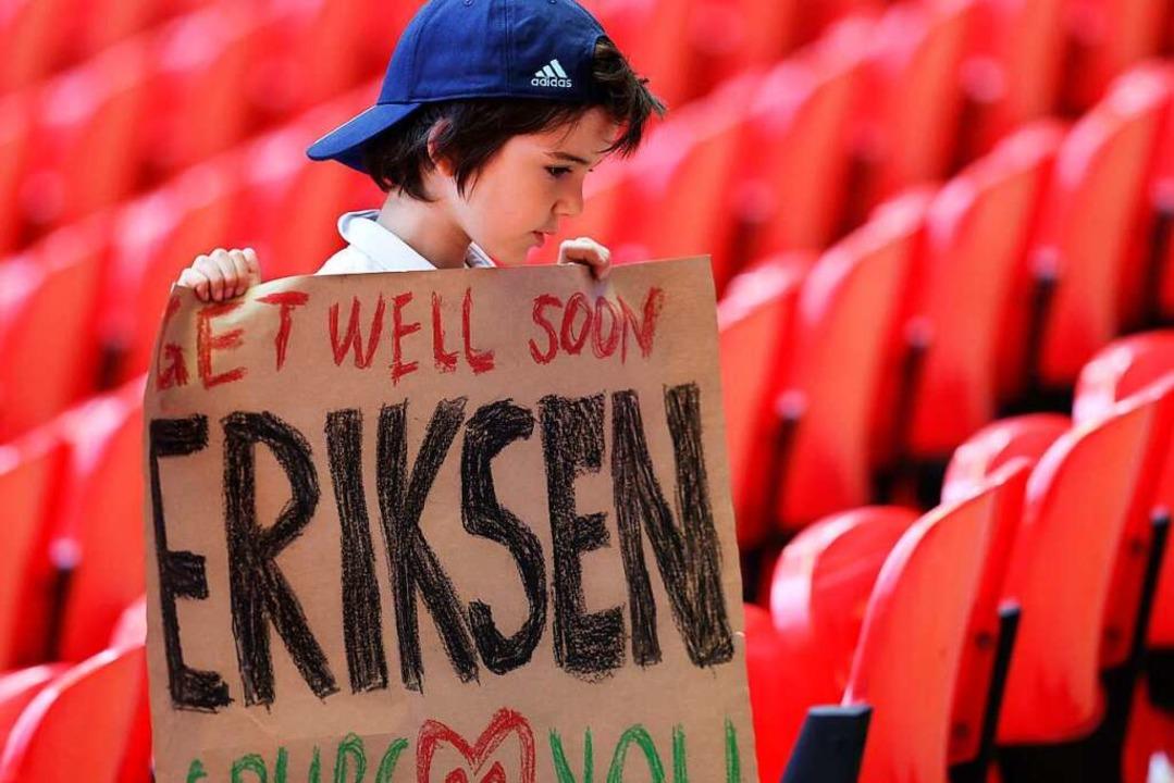 Ein junger Fan trägt ein Plakat mit Au... gegen Finnland zusammengebrochen war.  | Foto: Catherine Ivill (dpa)