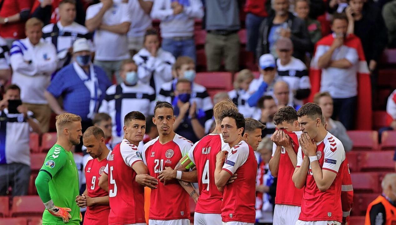 Teamkollegen schirmen das Geschehen um..., Zuschauer im Stadion sind betroffen.  | Foto: FRIEDEMANN VOGEL (AFP)
