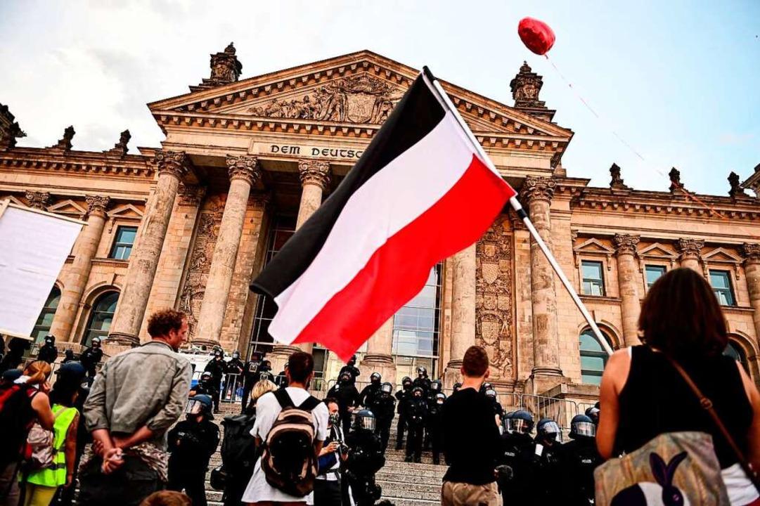 Ein Demonstrant schwenkt vor dem Berliner Reichstag die Reichsflagge.  | Foto: Fabian Sommer (dpa)