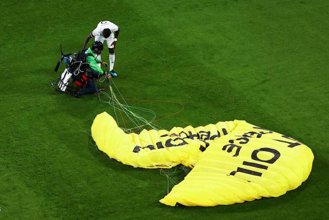 Ein deutscher Spieler kümmert sich um den Aktivisten.  | Foto: Christian Charisius (dpa)