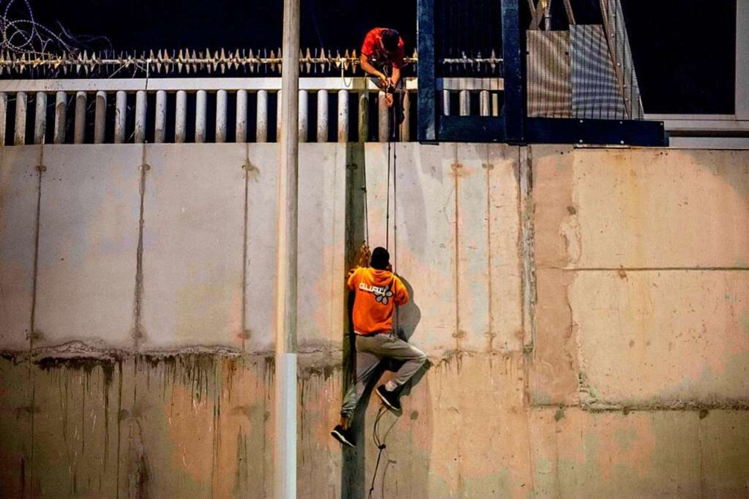 Ein Flüchtling erklimmt die Mauer in Ceuta.    Foto: BRAIS LORENZO via www.imago-images.de