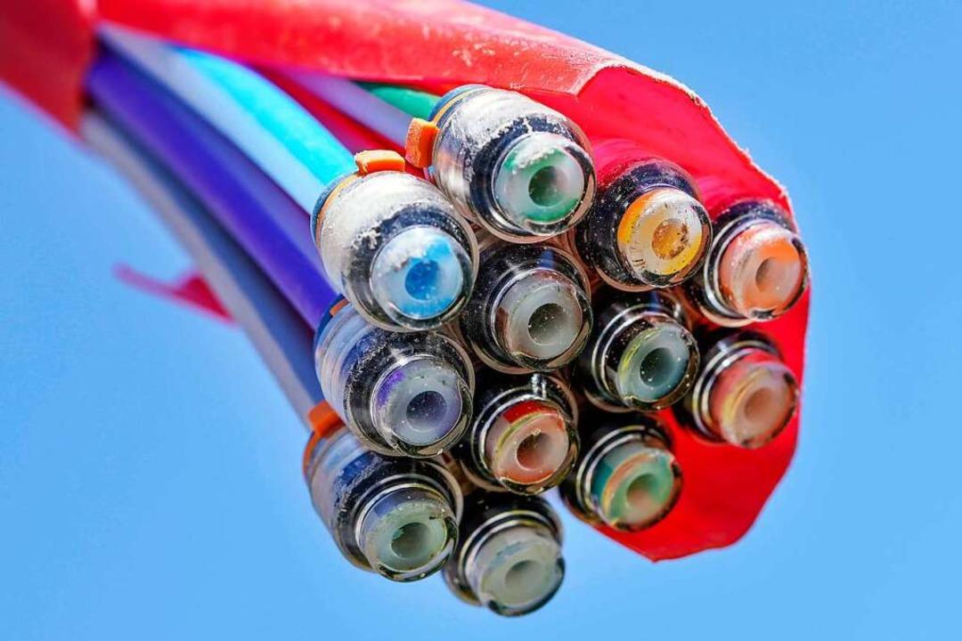 Ein Bündel mit Umhüllungen für Glasfaserkabel hängt vor dem blauen Himmel.  | Foto: Uwe Anspach (dpa)