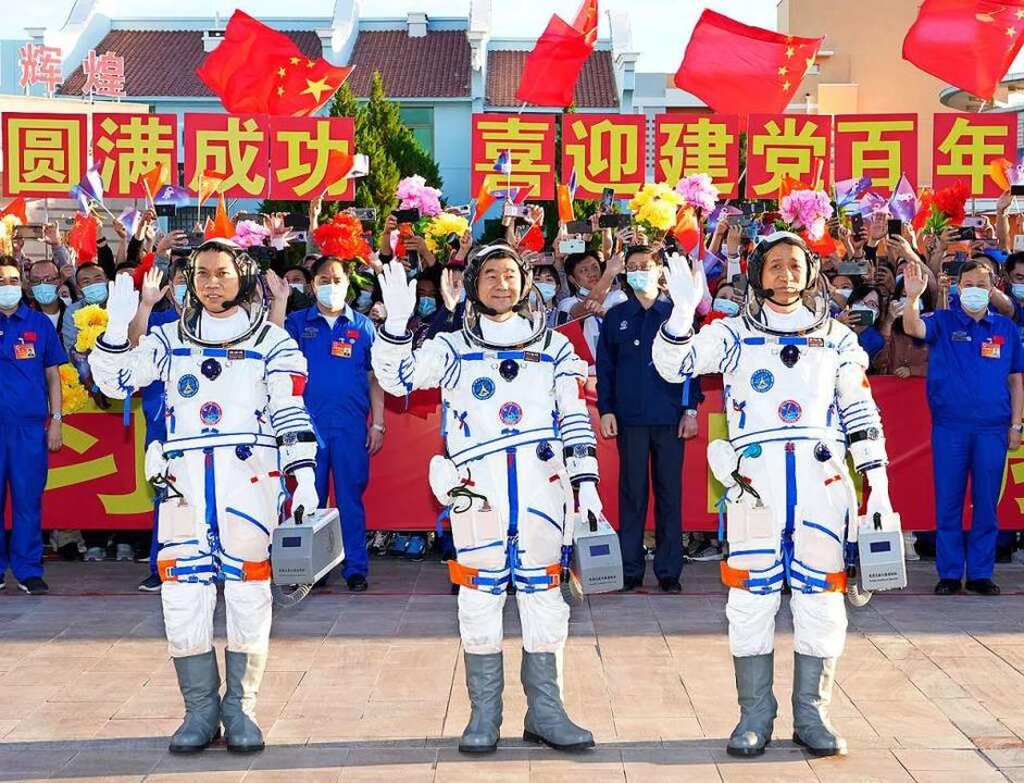 Die Astronauten Tang Hongbo,  Liu Bomi...heng (von links) winken vor dem Start.    Foto: Li Gang (dpa)