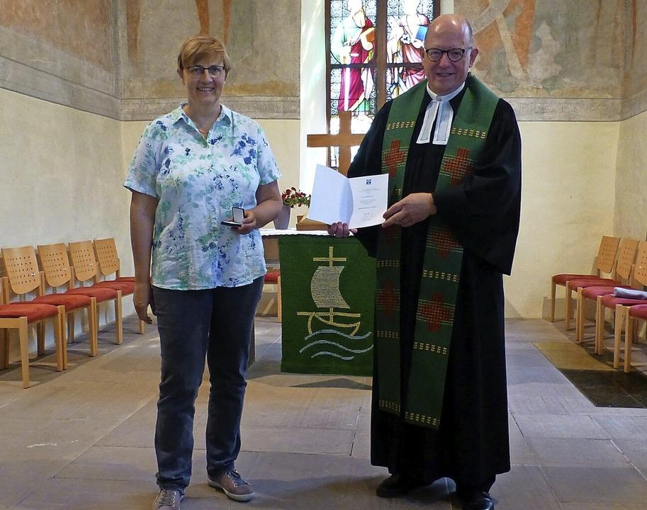 Pfarrer  Jochen Eber überreicht  Adelh...d des Alten- und Krankenpflegevereins.    Foto: Vera Winter
