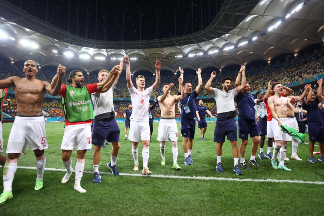 Die Schweizer Spieler jubeln nach dem Sieg im Elfmeterschießen.  | Foto: Marko Djurica (dpa)