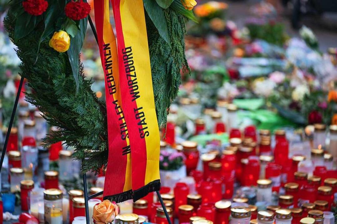 Trauerkerzen und Blumen  liegen vor einem Kaufhaus in der Innenstadt.  | Foto: Nicolas Armer (dpa)