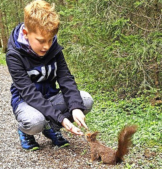 Marlon füttert ein EIchhörnchen.    Foto: Privat