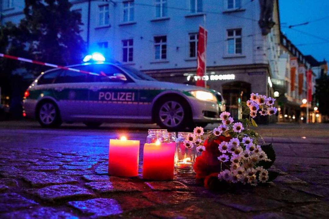 Kerzen und Blumen erinnern in Würzburg...ie infolge der Attacke gestorben sind.  | Foto: ARMANDO BABANI (AFP)