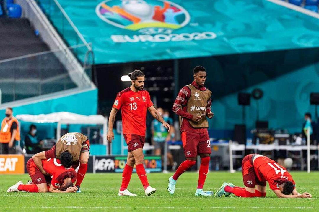 Die Schweizer wehrten sich lange tapfe..., tief enttäuscht gehen sie vom Platz.  | Foto: Jean-Christophe Bott (dpa)