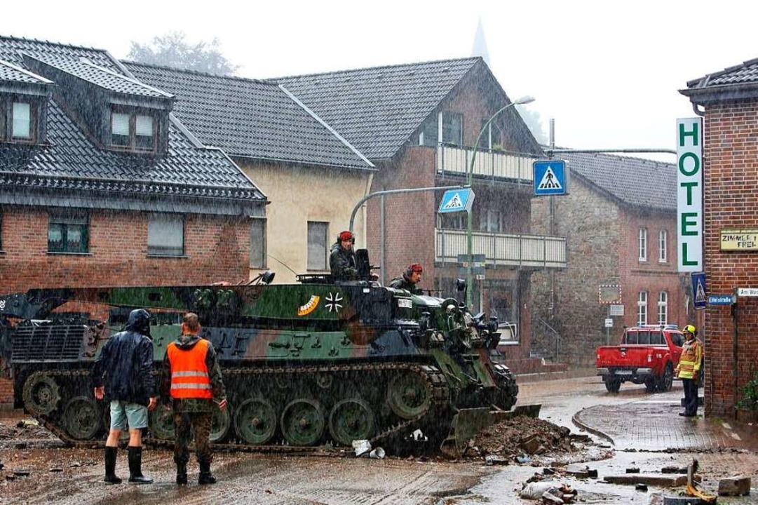 In Aachen räumt ein Einsatzfahrzeug der Bundeswehr Geröll von der Straße.    Foto: Dagmar Roeger (dpa)