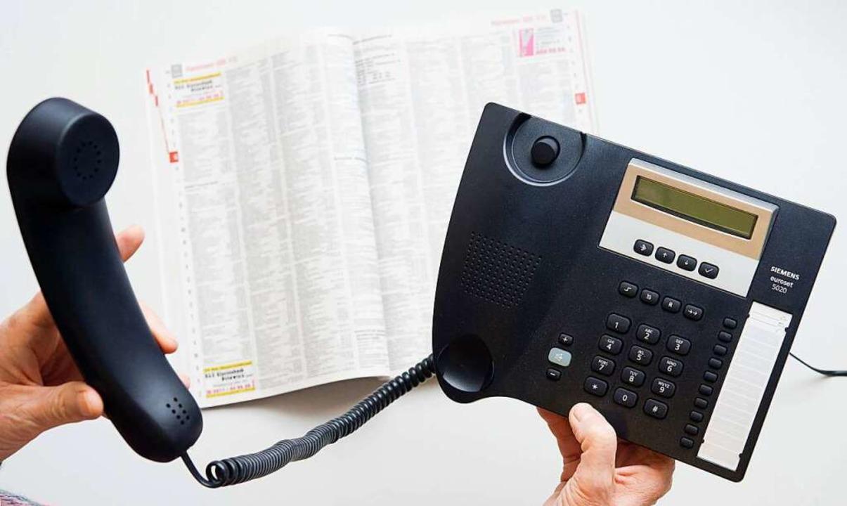 Weil ein Festnetzkabel der Telekom ris...zt vergeblich nach ihrem Telefonhörer.    Foto: Julian Stratenschulte (dpa)