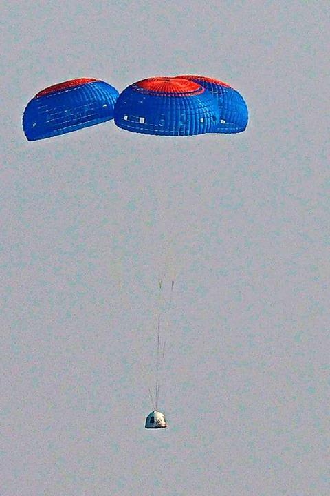 An drei Fallschirmen schwebt die Raumkapsel zurück zur Erde.  | Foto: JOE RAEDLE (AFP)