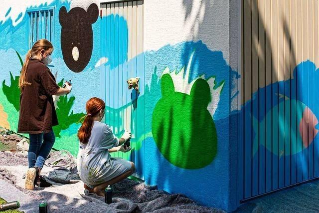 Schulkinder lernen, wie Graffiti-Künstler arbeiten und besprühen eine Garage mit Tiermotiven