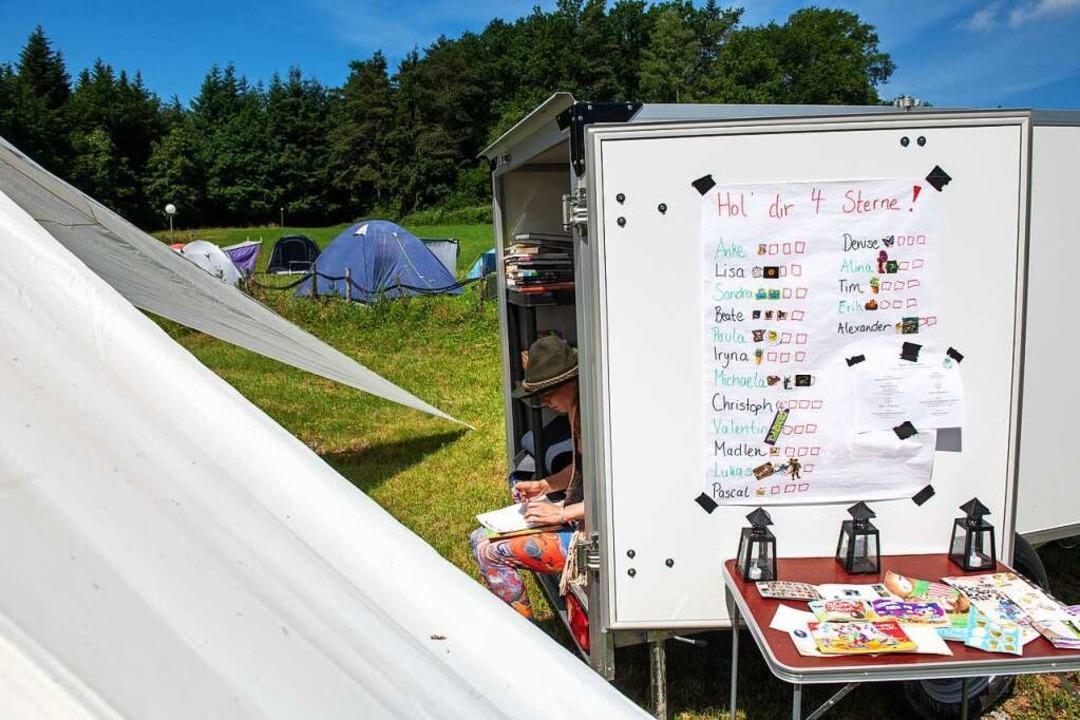 Veranstalterin Sandra sitzt einem Anhä... Sterneliste eines Ferienlagers hängt.    Foto: Stefan Puchner (dpa)