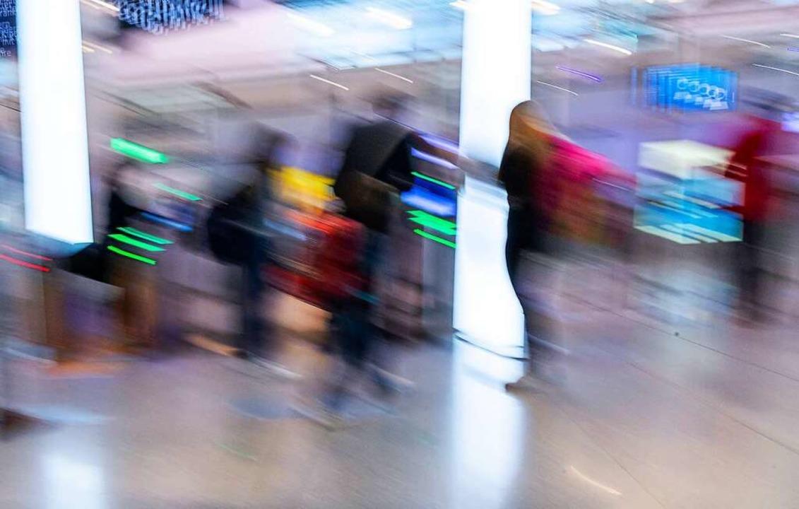 Passagiere stehen am Flughafen München an der Sicherheits-Kontrolle.  | Foto: Peter Kneffel (dpa)