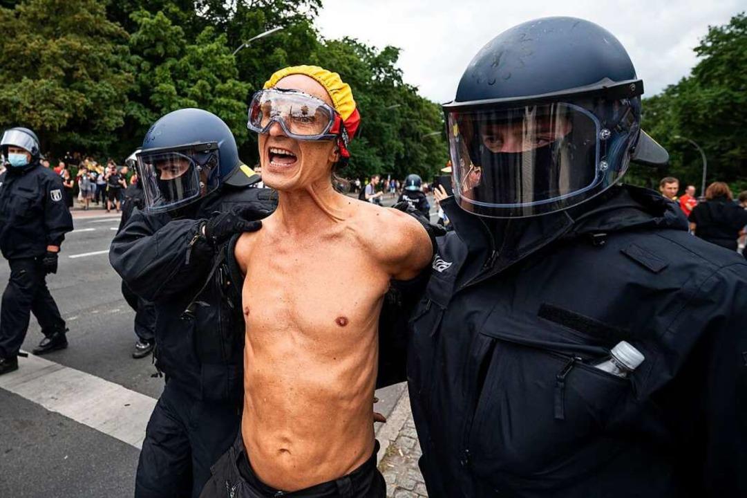 Die Polizei nimmt einen Demonstranten ...Demonstration an der Siegessäule fest.  | Foto: Fabian Sommer (dpa)