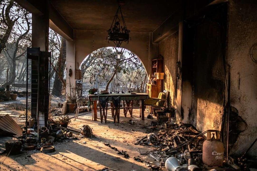Anwohner bekämpfen das Feuer.  | Foto: Angelos Tzortzinis (dpa)
