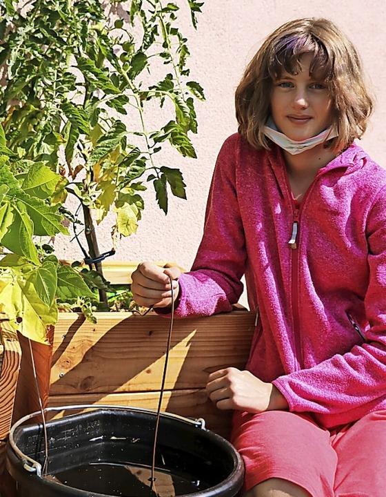 Alische präsentiert das Bewässerungssy...lanzen, die in Pflanzkübeln  gedeihen.  | Foto: Martha Weishaar